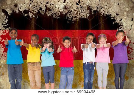 Elementary pupils smiling showing thumbs up against germany flag in grunge effect