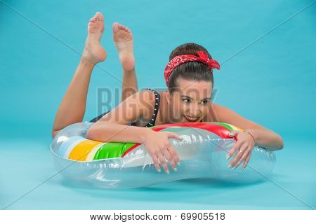 Beautiful girl with pretty smile in pinup style lying on inflata