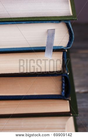 Stack of colorful hardback and paperback books, close-up, on gray background