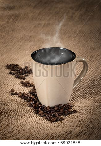 Steaming Cup Of Coffee And Coffee Beans