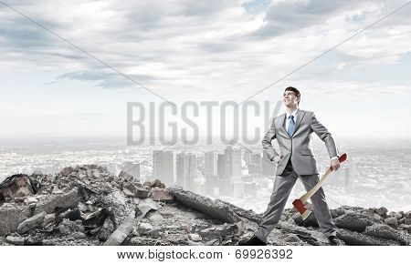 Man with axe on the top of garbage hill