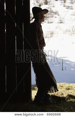 Vaquero que se inclinan en la puerta del granero