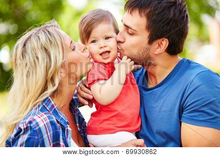 Careful parents kissing their small daughter