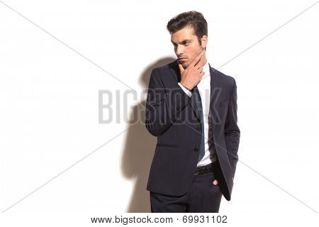 elegant business man thinking and looks away to his side on white studio background