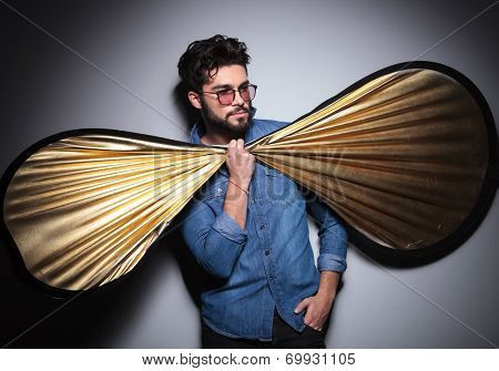 funny picture of young fashion man holding a big bow tie and looks to side