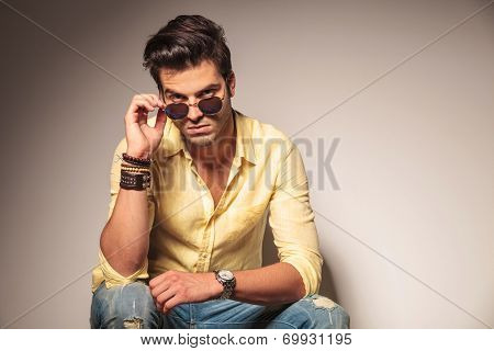 fashion man taking off his sunglasses and looks to the camera while seated on chair