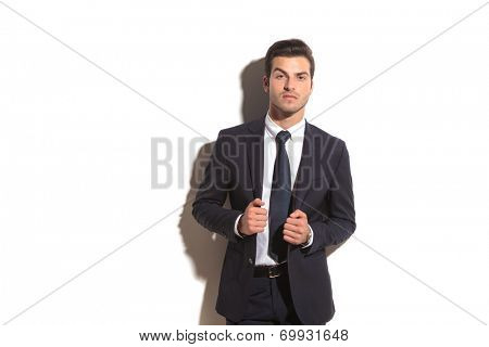sexy elegant business man leaning against white wall and pulls his coat's collar