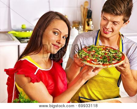 Young happy family cooking pizza at kitchen.