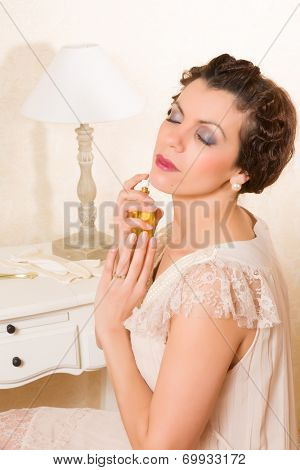Beautiful vintage 1920s woman applying perfume in her boudoir