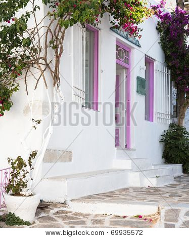 Typical Greek House With Flowers In The Entrance On The Cyclades.