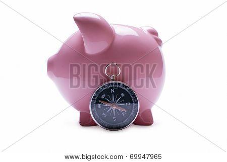 Pink Piggy Bank Next To A Vintage Compass