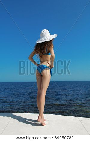 Beautiful Slim Girl In White Hat Over Blue Sky. Enjoyment. Fashion Model Woman In Bikini Relaxed.