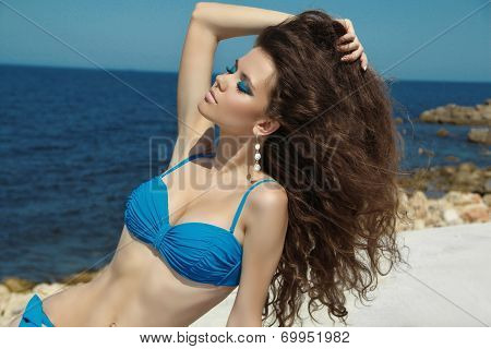 Sunbathing Tanned Beautiful Brunette Woman With Long Wavy Hair On The Beach