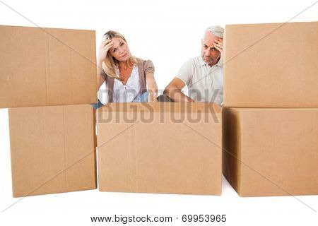 Stressed couple looking at moving boxes on white background
