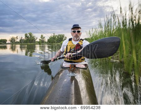 senior paddler in a racing sea kayak  on a calm lake, Fort Collins, Colorado