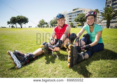 Fit mature couple tying up their roller blades on the grass on a sunny day