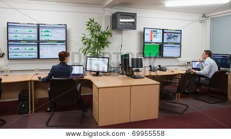 Technicians sitting in office running diagnostics in large data center