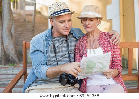 Happy tourist couple looking at map on a bench in the city on a sunny day