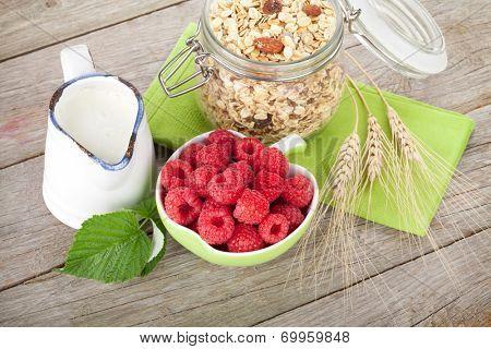 Healty breakfast with muesli, berries and milk. On wooden table