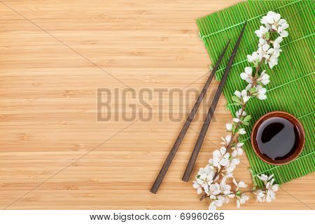 Chopsticks, sakura branch, soy sauce and bamboo mat on wooden table with copy space