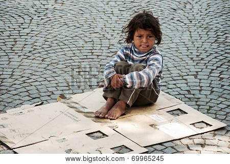 Unknown homeless kid sitting on the street