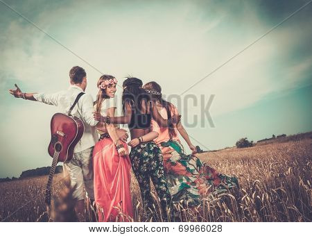 Multi-ethnic hippie friends with guitar in a wheat field