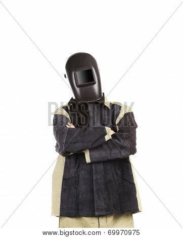 Welder in mask with arms crossed.