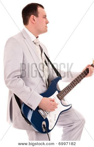 Man In Grey Suit Playing Guitar