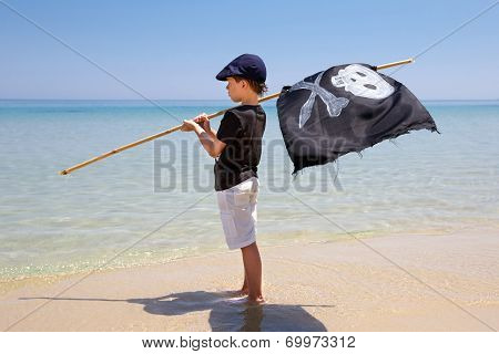 Cute boy dressed as pirate on tropical beach