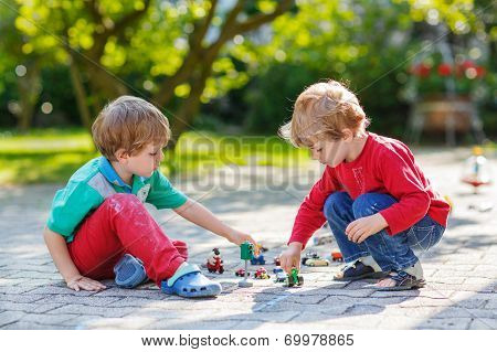 Two Little Boys Playing With Car Toys