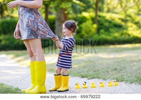Mother And Little Adorable Daughter In Yellow Rubber Boots, Family Look