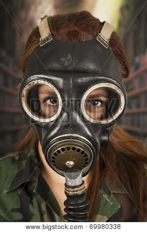 Young girl wearing military uniform and gas mask