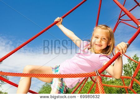 Girl hangs on red net ropes with two arms