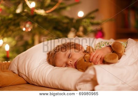 Little Cute Blond Boy Sleeping Under Christmas Tree