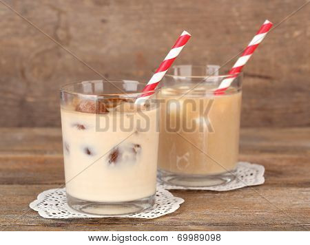 Iced coffee with milky ice cubes and cold milk with coffee ice cubes in glasses on wooden background