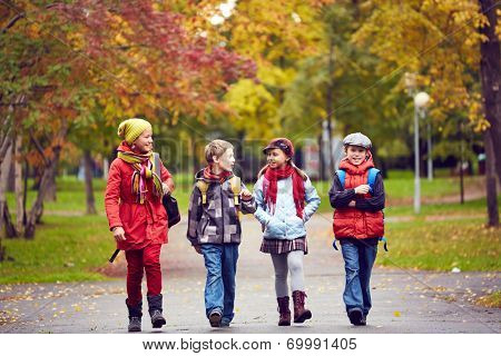 Portrait of happy schoolkids talking while going to school