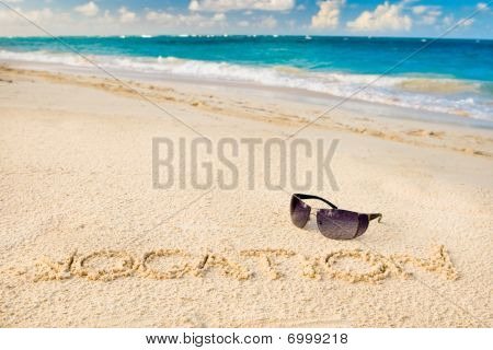Óculos de sol preto na praia de areia branca e a palavra vocação