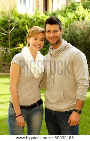 Young loving couple hugging and smiling outdoors, looking at camera.