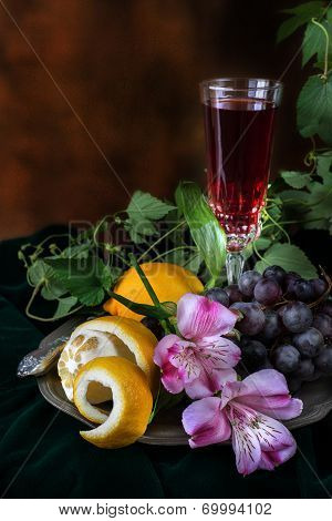 Still Life In Antique Style With A Glass Of Wine, Grapes And Two Lemons