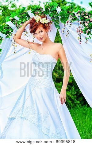 Beautiful bride with chaming red hair stands under the wedding arch. Wedding dress and accessories. Wedding decoration.