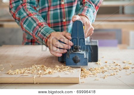Midsection of carpenter working with electric planer on wooden plank in workshop