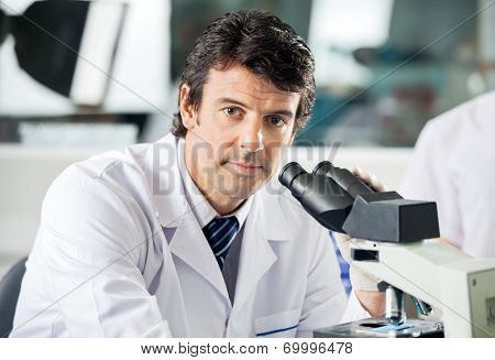 Portrait of mid adult male scientist using microscope in laboratory