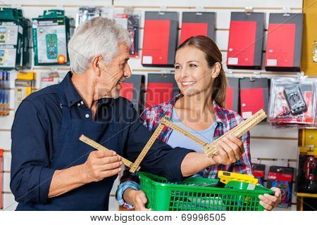 Happy male worker showing folding ruler to customer in hardware store