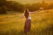 stock photo of beatitudes  - Happy young woman in the field with a bouquet of flowers