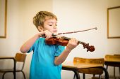 stock photo of violin  - Cute pupil playing violin in classroom at the elementary school - JPG