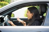 image of pissed off  - Closeup portrait angry young sitting woman pissed off by drivers in front of her and gesturing with hands isolated city street background - JPG