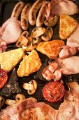 image of hash  - Cooking breakfast for a family with a closeup overhead view of bacon hash browns sausages tomato and mushrooms sizzling on a hot griddle - JPG