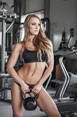 picture of kettlebell  - Blonde fitness model posing with kettlebell in gym - JPG