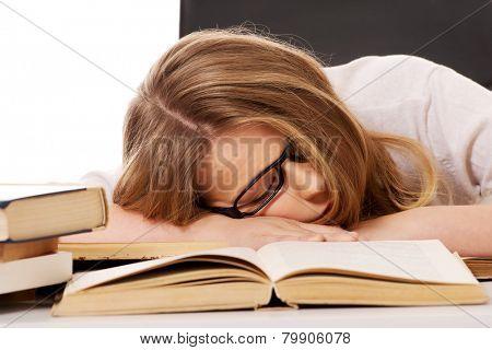 Exhausted teenage woman sleeping on the desk