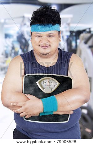 Obesity Person Holding Scale In Fitness Center